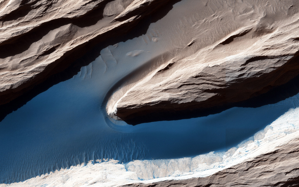 The wind has carved features, called yardangs, one of many in this scene, and deposited sand on the floor of shallow channels between them as seen by NASA's Mars Reconnaissance Orbiter spacecraft.