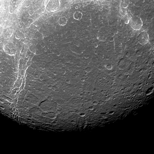 Dione reveals its past via contrasts in this view from NASA's Cassini spacecraft. The features visible here are a mixture of tectonics (bright, linear features and impact cratering) the round features, which are spread across the entire surface.
