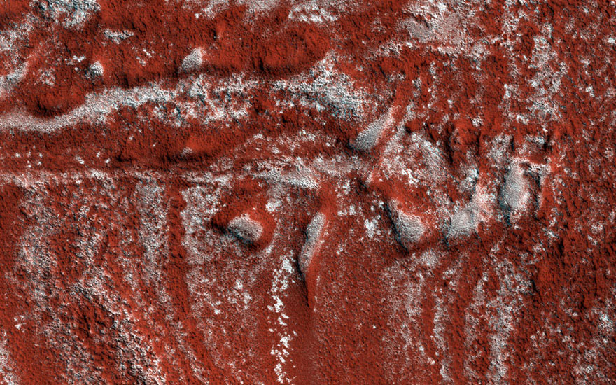 These North Polar layered deposits, composed of ice, captured by NASA's Mars Reconnaissance Orbiter spacecraft, show what looks like drag folds, where rock layers bend (fold) before they break in a fault.