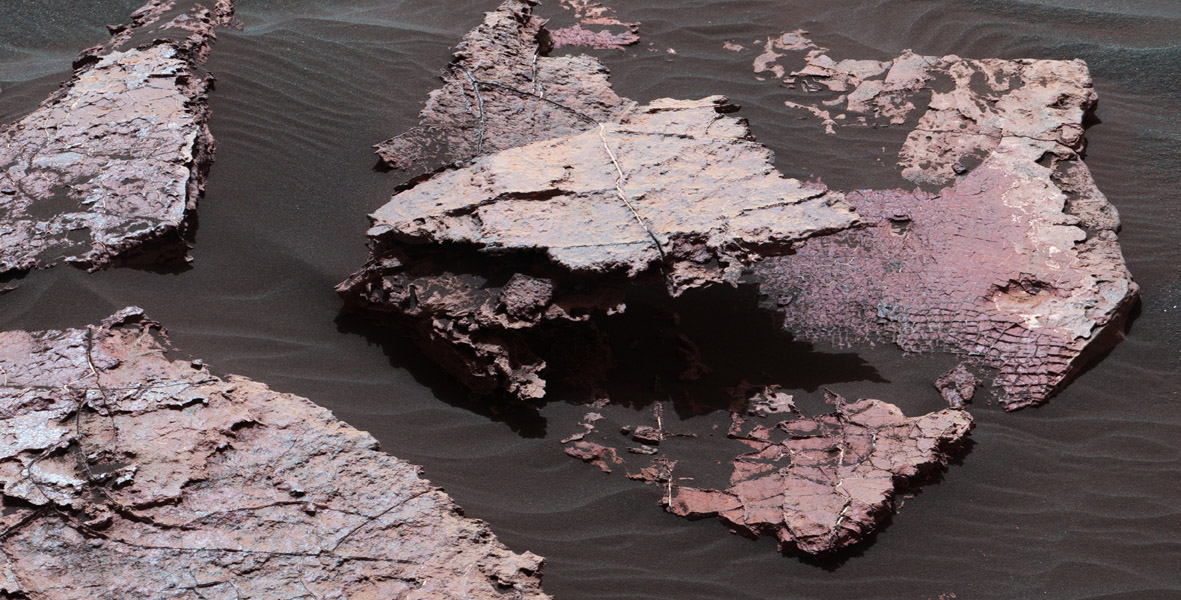 A grid of small polygons on the Martian rock surface near the right edge of this view may have originated as cracks in drying mud more than 3 billion years ago. Multiple images of this view were combined for this view from NASA's Curiosity Mars rover.