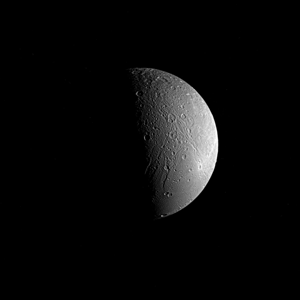 Saturn's moon Dione is captured in this view from NASA's Cassini spacecraft, half in shadow and half in light. Sinuous canyons carve interconnected paths across the moon's icy landscape. The Cassini spacecraft ended its mission on Sept. 15, 2017.