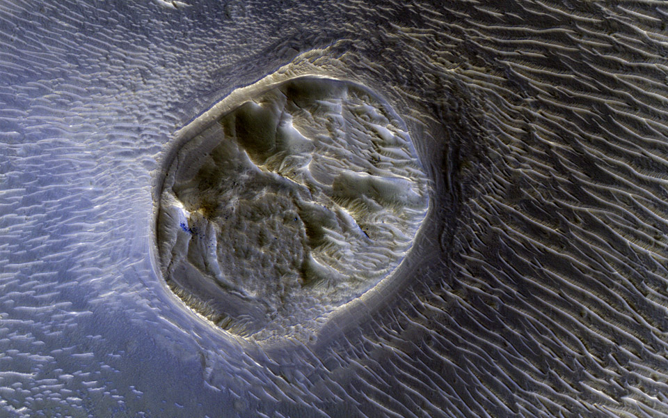This small mesa is one of several surrounded by sand dunes in Noctis Labyrinthyus, an extensively fractured region on the western end of Valles Marineris, as seen by NASA's Mars Reconnaissance Orbiter.