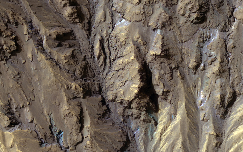 The sources of channels on the north rim of Hale Crater show fresh blue, green, purple and light toned exposures under the the overlying reddish dust, captured by NASA's Mars Reconnaissance Orbiter.