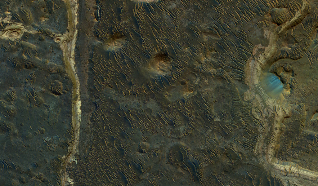 Holden Crater was once filled by at least two different lakes. The sediments deposited in those lakes are relatively light-toned where exposed in this observation from NASA's Mars Reconnaissance Orbiter.