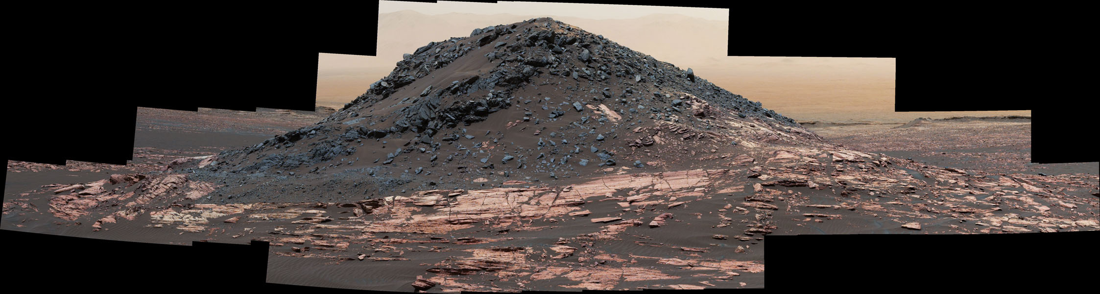 This dark mound, called 'Ireson Hill,' rises about 16 feet (5 meters) above redder layered outcrop material of the Murray formation on lower Mount Sharp, Mars, near a location where NASA's Curiosity rover examined a linear sand dune in February 2017.