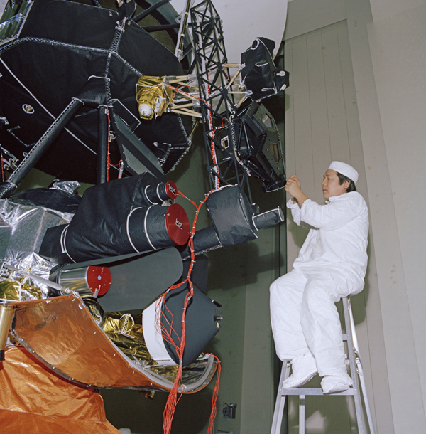 An engineer works on vibration acoustics and pyro shock testing for one of NASA's Voyager spacecraft on November 18, 1976. Several of the spacecraft's science instruments are visible at left.
