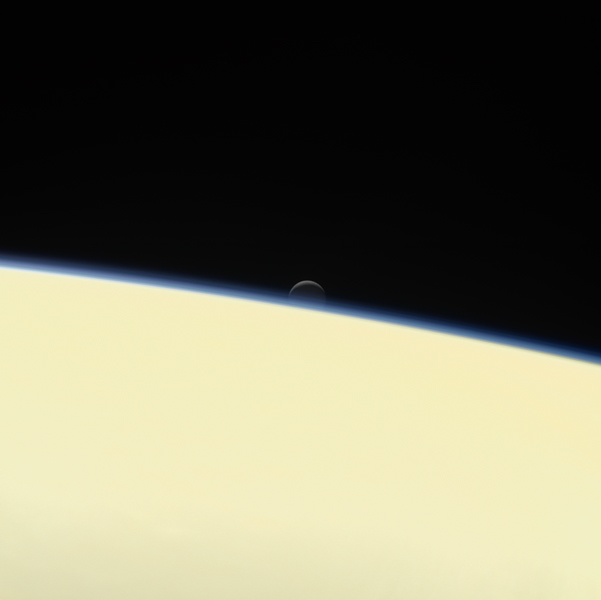 Saturn's active, ocean-bearing moon Enceladus sinks behind the giant planet in a farewell portrait from NASA's Cassini spacecraft. This view of Enceladus was taken by the Cassini spacecraft on Sept. 13, 2017.