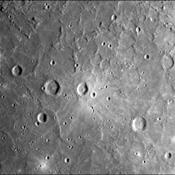 A dark, smooth, relatively uncratered area on Mercury was photographed two hours after NASA's Mariner 10 flew by the planet. The prominent, sharp crater with a central peak is 30 kilometers (19 miles) across.