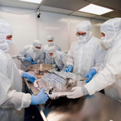 Investigators from University of Washington, Johnson Space Center, and Lockheed Martin Missiles and Space, Denver, Colorado, inspect a canister and sample collector soon after opening a container with Stardust material in a laboratory at the JSC.