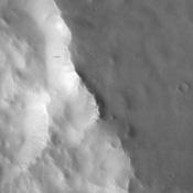This image, captured by NASA's 2001 Mars Odyssey spacecraft, shows that this portion of the rim of Henry Crater has numerous dark streaks located on the slopes of the inner crater wall.