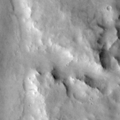 This image, taken by NASA's Mars Odyssey spacecraft, shows a cratered highland region called Arabia Terra. The center right side of the image shows a branch of the valley network Naktong Vallis cutting into the eastern rim of an unnamed crater.