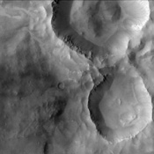 This region of Terra Meridiani, imaged by NASA's Mars Odyssey, shows an old, heavily degraded channel that appears to terminate abruptly at the rim of a 10 km diameter crater, suggesting that the impact crater was created after the channel was formed.