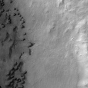 This image taken by NASA's Mars Odyssey spacecraft shows a portion of Maunder Crater with a number of interesting features including a series of barchan dunes that are traveling from right to left and gullies.
