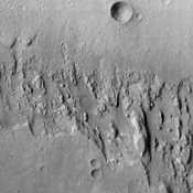 This image from NASA's Mars Odyssey spacecraft shows signs of layering exposed at the surface in a region of Mars called Terra Meridiani. The brightness levels show daytime surface temperatures.