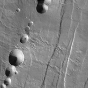 Tantalus Fossae, seen in this image from NASA's Mars Odyssey spacecraft, is a set of long valleys on the eastern side of Alba Patera. These valleys are referred to as grabens and are formed by extension of the crust and faulting.