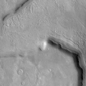 This NASA Mars Odyssey image shows several 'fretted' channels within Deuteronilus Mensae in the northern plains of Mars. These linear troughs appear to have been extensively modified by surficial processes.