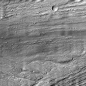 The scoured grooves in the catastrophic outflow channels shown in this image from NASA's Mars Odyssey spacecraft formed hundreds of million of years ago and have the appearance of wood grain. They now host dune-like ripples of windblown material.