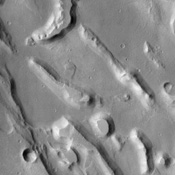 The jumble of eroded ridges and mesas seen in this NASA Mars Odyssey image occurs within Ares Vallis, one of the largest catastrophic outflow channels on the planet. Floods raged through this channel, pouring out into the Chryse Basin to the north.