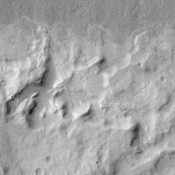 This scene from NASA's Mars Odyssey spacecraft shows several interesting geologic features associated with impact craters on Mars.