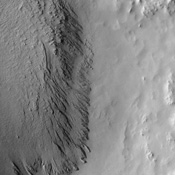 This image from NASA's Mars Odyssey shows deposits in a crater located in Arabia Terra. Arabia is generally dust covered and dark streaks or dust avalanches are present in the crater walls.
