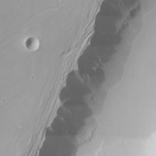 A large streamlined island in Kasei Vallis, as seen in this NASA Mars Odyssey image, shows evidence of scour on its surface, probably from floods that preceded the formation of the island.