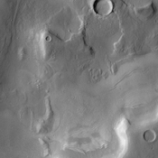 A broad channel in the Deuteronilus Mensae region, shown in this NASA Mars Odyssey image, displays the strange landforms common to the northern mid-latitudes where ground ice likely plays a role in their formation.
