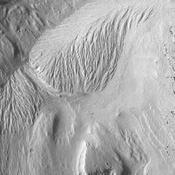 The eroded, layered deposit in this NASA Mars Odyssey image of Gale Crater is a mound of material rising 3 km (about 2 miles) above the crater floor. It has been sculpted by wind and possibly water to produce the dramatic landforms seen today.