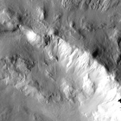 The slumping of materials in the walls of this impact crater imaged by NASA's Mars Odyssey spacecraft illustrates the continued erosion of the Martian surface. Small fans of debris as well as larger landslides are observed throughout the image.