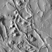 Tall narrow ridges snake between mesas and buttes in this image from NASA's Mars Odyssey. Where one such ridge crosses a flat-topped mesa (in the lower center of the image), the mesa surface is split into two surfaces of different heights.