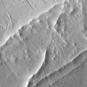 Hummocky, textured terrain within lava flows northwest of Pavonis Mons, one of the Tharsis volcanoes, is shown in this image from NASA's Mars Odyssey spacecraft.