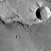 This image shows a section of Nirgal Vallis. In this image a crater has been formed across the vallis. The crater formation postdates the channel formation.