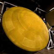 This image shows NASA's Mars Science Laboratory heat shield, and a spacecraft worker at Lockheed Martin Space Systems, Denver. It is the largest heat shield ever built for descending through the atmosphere of any planet.
