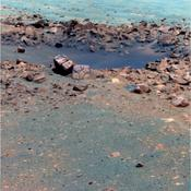 This false-color image, taken by the panoramic camera on NASA's rover Opportunity, shows the rock 'Chocolate Hills,' perched on the rim of the 10-meter (33-foot) wide 'Concepcion' crater. This rock has a thick, dark-colored coating resembling chocolate.