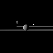 NASA's Cassini spacecraft observes three of Saturn's moons set against the darkened night side of the planet. Seen here are Rhea, closest to Cassini, Enceladus to right of Rhea, and Dione, left of Rhea.