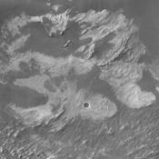 This image taken by NASA's 2001 Mars Odyssey shows a portion of the floor of Melsa Chasma. Wind blown material is located in lows between layered floor materials.