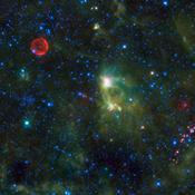 This image from NASA's Wide-field Infrared Survey Explorer takes in several interesting objects in the constellation Cassiopeia which are not easily seen in visible light. The red circle visible at upper left is SN 1572, often called Tycho's Supernova.