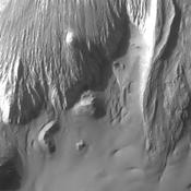 This image from NASA's 2001 Mars Odyssey shows a portion of the floor of Ganges Chasma. Eroded deposits and sand dune forms are common features of Ganges Chasma.