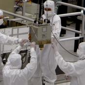 Members of NASA's Mars Science Laboratory team carefully steer the hoisted Chemistry and Mineralogy (CheMin) instrument during its June 15, 2010, installation into the mission's Mars rover, Curiosity.