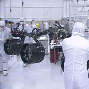 In this image taken from a video clip, NASA's Curiosity rover's wheels are shown hoisted on a pink crane and moving closer to the rover's body. Video is available at the Photojournal.