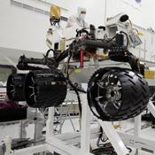 This image was taken in the cleanroom where NASA's Curiosity rover is being assembled. It shows the rover, which is about the size of an SUV, hoisted on a white lift, with its black wheels suspended in the air.
