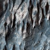 In this image from NASA's Mars Reconnaissance Orbiter, there are at least two distinct geologic units, a light-toned bedrock and a surface veneer of dark-toned material that contains sand dunes.