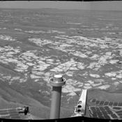 This mosaic of images from NASA's Mars Exploration Rover Opportunity shows surroundings of the rover's location. The terrain includes light-toned bedrock and darker ripples of wind-blown sand.