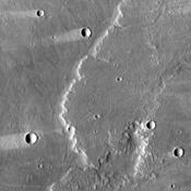 This image from NASA's Mars Odyssey shows lava flows of Alba Mons and windstreaks behind craters in the area. Windstreak tail directions indicate winds from the East and East-Northeast.