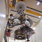 Technicians transfer NASA's Juno spacecraft from its rotation fixture to the base of its shipping container in preparation for a move to environmental testing facilities.  Juno's main engine, its cover closed, is visible on the spacecraft's underside.