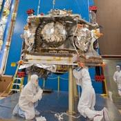 Technicians lift NASA's Juno spacecraft onto a dolly prior to the start of a round of acoustical testing.