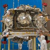 Technicians position NASA's Juno spacecraft on a dolly prior to the start of a round of acoustical testing.