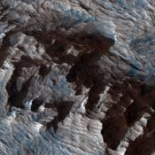 This image from NASA's Mars Reconnaissance Orbiter shows an area of layered deposits in Candor Chasma. Sheets and dunes of dark-toned sand cover the light-toned, layered bedrock.