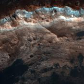 NASA's Mars Reconnaissance Orbiter shows the surface outside this large crater is relatively dark, while the interior wall of the crater exposes lighter, layered bedrock of diverse colors.