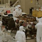 In this photograph, technicians and engineers inside a clean room at NASA's Jet Propulsion Laboratory, Pasadena, Calif., position NASA's Sample Analysis at Mars (SAM) above the mission's Mars rover, Curiosity, for installing the instrument.