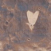 This picture of a heart-shaped feature in Arabia Terra on Mars was taken on May 23, 2010, by NASA's Mars Reconnaissance Orbiter. A small impact crater near the tip of the heart is responsible for the formation of the bright, heart-shaped feature.